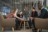 Diverse group of executives meeting in office sharing creative ideas. Young people having a meeting in lobby. - Stock Image - EJR1K5