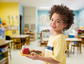 Mixed race boy having lunch at school - Stock Image - D93DH2