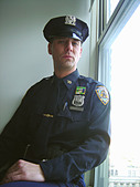 Portrait of a New York City Police Officer Near a Window - Stock Image - AT6ATH