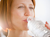 Close-up of redhead woman drinking water - Stock Image - C3HJ31