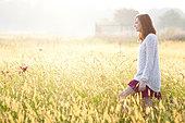 Young woman walking in field - Stock Image - DT34EK