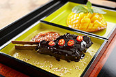 Braised lamb chop with chocolate, mango and cardamom - Stock Image - BJJW6M