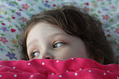 A small child in bed with blankets pulled up to eyes. - Stock Image - CNF0JY