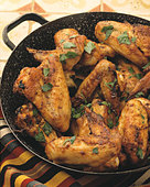 Crispy fried chicken wings with herbs in the pan - Stock Image - BJH6D5