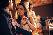 Young woman with a glass of wine talking to a man at the bar - Stock Image - D554W1