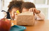 African siblings looking in bag lunch - Stock Image - B3AY66