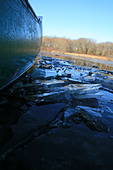 detail of the side of a green canoe breaking through icy water - Stock Image - C9DEPA
