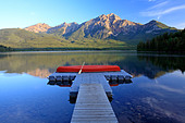 Red canoe on dock at Pyramid Lake with Pyramid mountain, Jasper National Park, Alberta, Canada. - Stock Image - CFBXN5