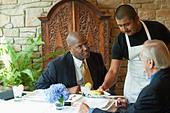 Businessmen having lunch in restaurant - Stock Image - D1PMHT