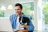 Man with dog on lap using laptop - Stock Image - D5WYAE
