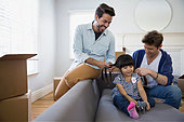 Homosexual couple fixing daughter hair sofa moving boxes - Stock Image - ERBPBH