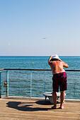 Plane spotter on the peir at Finikoudas, Larnaca, Cyprus. - Stock Image - ECYKMD