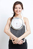 Portrait of cheerful Asian woman holding weight scale against white background - Stock Image - D00029