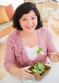 Hispanic woman eating salad for lunch - Stock Image - CECH6W