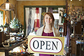 A woman standing in an antique store holding an OPEN sign Displays of goods all around her - Stock Image - DT1J0E