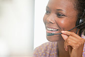 Close up of happy businesswoman using headset - Stock Image - DYF6MC