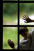 silhouette of person behind glass window with hands on panes of glass - Stock Image - B3BG4J
