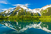 Person canoeing in small lake in Portage Valley of Chugach National Forest during Spring in Southcentral Alaska - Stock Image - C2THBJ