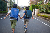 Boys holding hands and running, Tokyo Prefecture, Honshu, Japan - Stock Image - BRY85H