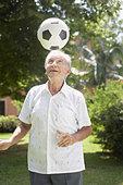 Senior man outdoors balancing soccer ball on head - Stock Image - B0KAM5