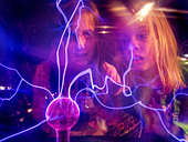 Girls 11 and 7 years old fascinated by tesla plasma ball, Tegelen, the Netherlands - Stock Image - CP74R9