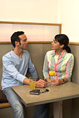 couple sitting in cafe talking to each other - Stock Image - A3KYT1
