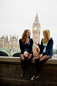 Two teenage girls sitting near Big Ben, having lunch - Stock Image - C74001