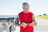 Fit mature man checking the time on the pier - Stock Image - E659FB