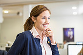 Smiling businesswoman with hand on chin looking away in office - Stock Image - E3MJ30