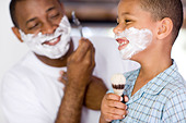 Father and son with shaving foam on their faces. The father is shaving whilst his son is singing into a shaving brush. - Stock Image - B6DYD7