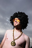 Funny guy with afro wig glasses and bling - Stock Image - BA0GFK