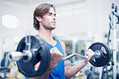 Man lifting barbell in gymnasium - Stock Image - CRBEB3