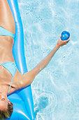 Woman in bikini on flotation device in pool with beverage - Stock Image - AA6B7K