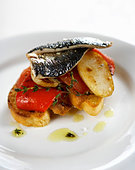 Fried sardines on potatoes and peppers - Stock Image - BJP7DM