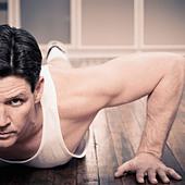 Man doing push ups indoors - Stock Image - D5700J