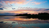 Southport, Merseyside, UK. 29th June, 2015. A stunning sunrise over the RSPB nature reserve of 'Rimmers Marsh'.  A delightful balance of meadow land & wetlands provide a perfect habitat for holstein cattle & wetland birds.  ©Cernan Elias/Alamy Live News - Stock Image - EWMC1W