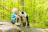 Boy sitting with dog in forest - Stock Image - CT0YJF