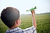 Boy playing with toy plane - Stock Image - B2R4YW