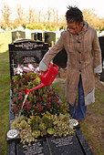 Woman tends the grave of her mother in an East London cemetery - Stock Image - AF2XKA