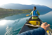 Paddling a canoe on an autumn morning on Chilko Lake, British Columbia - Stock Image - CFC2RY