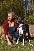 Woman walking dog in autumn leaves - Stock Image - D2AM8N