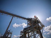 Worker standing on conveyor in quarry - Stock Image - CT19WY