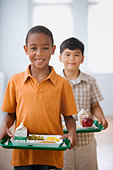 Students carrying lunch on trays in cafeteria - Stock Image - B6B1H4