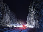 Stationary car with open door on snowy, rural road, at night - Stock Image - EYCYAK