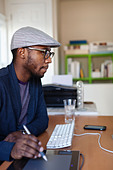 Black designer working at desk - Stock Image - CTH0XR