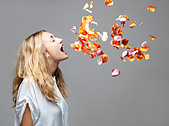 Young woman with mouth open an petals floating in mid air - Stock Image - DADJ80