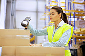Young woman using barcode reader in distribution warehouse - Stock Image - E0A9AP