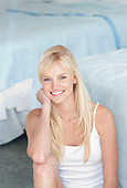 Female long blonde fringed hair, wearing black mascara, blue eyeliner and pink lipgloss, sitting in bedroom on the flowith one - Stock Image - CF5WBK
