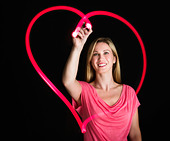 Woman drawing heart on black background - Stock Image - CWMGAM
