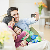 Family on couch posing for photograph - Stock Image - BAW0PN